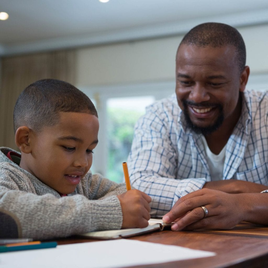 Smiling African-American man helping a boy write